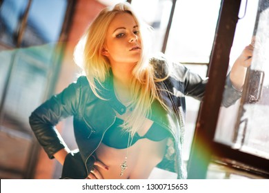 Beautiful and cute blond girl posing for photo in the loft photostudio
