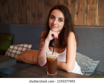 Beautiful cute brunette girl sitting in the cozy cafe near the window enjoying big cup coffee with straw and shy smiling