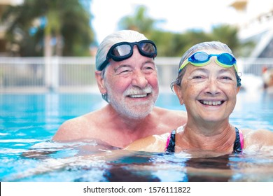 beautiful and cute close up of two seniors in the pool having fun together - fitness and healthy lifestyle - summertime together