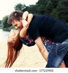 Beautiful cute couple on the beach near the water hugging