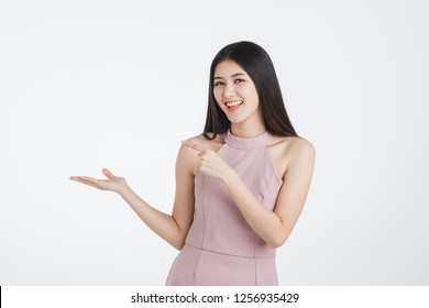 Beautiful cute face young asian girl  in pink dress, confident happy smile posing her empty hands with blank space in cheerful manner for advertising use, portrait shot isolated on white background.