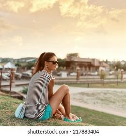 Beautiful cute fashionable girl sitting at sunset