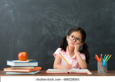 beautiful cute female children writing homework having problem and thinking about solution feeling difficulty in chalkboard background.
