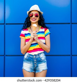 Beautiful cute funny amazing young hipster teen girl eating ice cream cone, laughs happy, bright casual wear, denim shorts, striped, colored T-shirt, rainbow, blue background, urban style, sunglasses