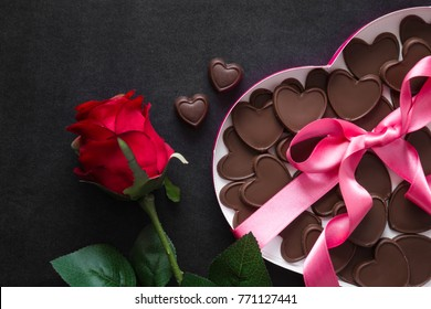 Beautiful, cute gifts for beloved. Red rose with chocolate hearts in the box of heart shape with pink ribbon on the dark table. Enjoying sweets. Valentine's day and relationships concept.