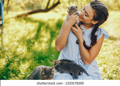beautiful and cute girl in blue dresses with beautiful hairstyles and make-up sitting in a sunny green garden and playing with a cats