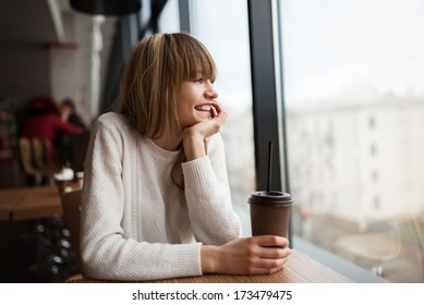 Beautiful cute girl in the cafe near the window with coffee smiling