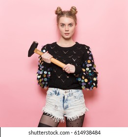 Beautiful cute girl holding heavy hammer in hands. Home repair and feminism concept.