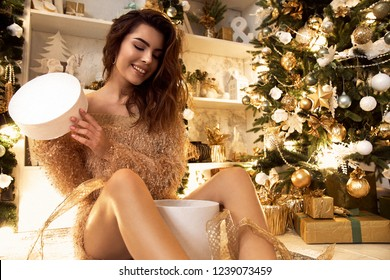 Beautiful cute girl opens a gift, hugs gifts, smiles and rejoices, decorates a Christmas tree with New Year's decorations. New Year makeup, hairstyle and bronze skin.