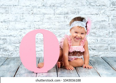 Beautiful and cute girl in a pink dress with the letter O. Emotional girl.