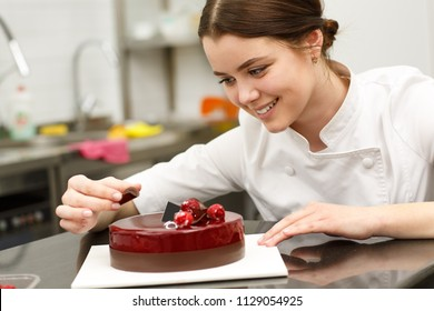 Beautiful and cute girl smiling and decorating glazed cake. Young confectioner wearing white uniform while working in confectionery. She baking delicious dark red with chocolate.