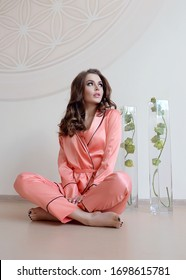 beautiful cute girl spends time at home in homemade silk clothes. This pyjama is a real costume, it is cozy, comfortable and beautiful to walk at home. The girl has light natural makeup