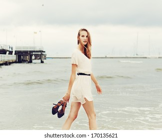 Beautiful cute girl summer walks along the beach barefoot with shoes in hands
