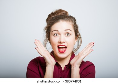 beautiful cute girl surprised isolated on a gray background