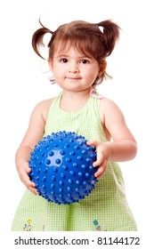 Beautiful cute happy toddler baby girl in green dress playing with blue spiky ball, isolated.