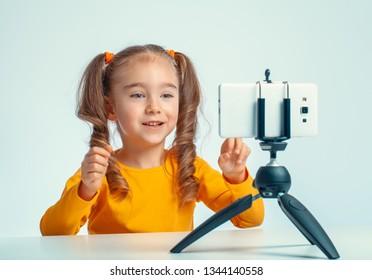 beautiful cute little blogger smiling, talking and gesturing to smartphone on tripod and recording a video for her followers on internet