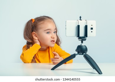 beautiful cute little blogger talking and gesturing to smartphone on tripod and recording a video for her followers on internet