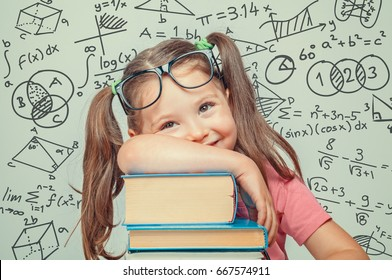 beautiful cute little genius girl with books and math formulas, problems around her