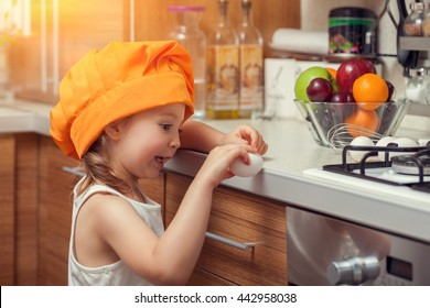 beautiful cute little girl with bonnet breaking an egg on countertop in kitchen