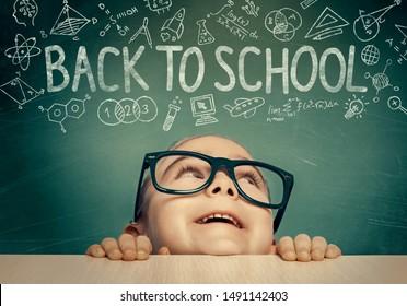 Schönes süßes kleines Mädchen mit Brillen, die sich unter dem Tisch verstecken, Blick zurück zu Schulwort und Illustrationen über ihrem Kopf. Kluges Studentenkonzept.
