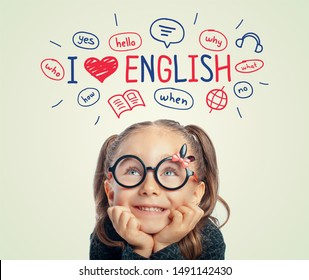 Beautiful cute little girl with eyeglasses looking at i love english word, illustrations and words above her head.  i love english concept.