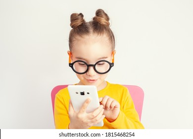 Beautiful cute little girl with eyeglasses holding smartphone in her hand and making gesture on screen. Child from alpha generation playing r using mobile app or playing game on smartphone. .