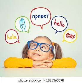Wunderschönes kleines Mädchen mit Brille, das hallo Wort auf Spanisch, Englisch, Russisch, Chinesisch und Amerikanische Gebärdensprache in Sprachballons anschaut. K-12 Fremdsprachenlernkonzept