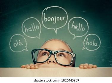 Wunderschönes kleines Mädchen mit Brillen, die sich unter dem Tisch verstecken und hallo Wort auf Französisch, Englisch, Spanisch, Portugiesisch und Deutsch in Sprachballons anschauen. K-12 Fremdsprachenlernkonzept