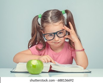 beautiful cute little girl with grin face pointing her finger at thick book and looking at camera