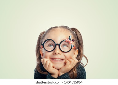 beautiful cute little girl with hands on face smiling and looking up. cheerful smart girl portrait