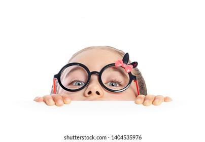 schönes süßes kleines Mädchen, das sich unter dem Tisch versteckt und die Kamera auf weißem Hintergrund merkwürdig anschaut. Fröhliches und spielerisches kleines Mädchen, das Verstecken und Suchen spielt