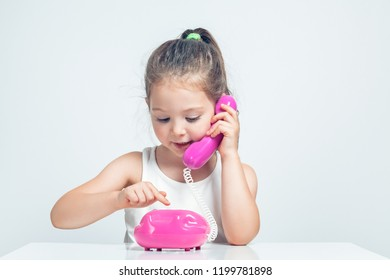 beautiful cute little girl holding toy telephone and dialing with happy expression