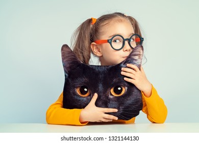 beautiful cute little girl kissing ear of cat shaped pillow