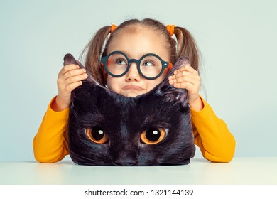 beautiful cute little girl looking up and holding ears of cat shaped pillow