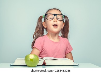 beautiful cute little girl memorizing with closed eyes when reading thick book