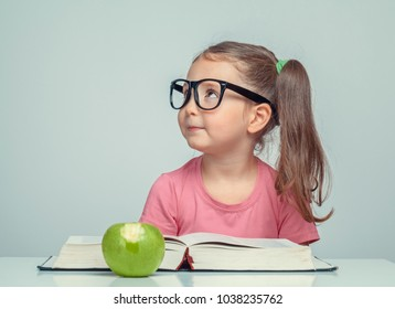 beautiful cute little girl next to thick book and green apple