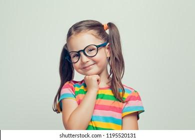 hübsches kleines Mädchen, das sich mit der Hand unter dem Kinn posiert und lächelt