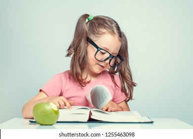 beautiful cute little girl reading and turning the pages of thick book