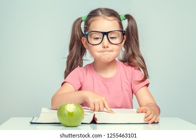 beautiful cute little girl reading thick book and pointing with her finger