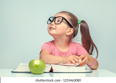 beautiful cute little girl with smiling face looking up and turning the page of book