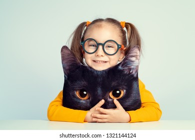 beautiful cute little girl smiling and hugging to cat shaped pillow