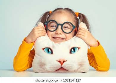 beautiful cute little girl smiling and holding ears of cat shaped pillow