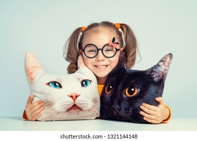 beautiful cute little girl smiling and hugging to cat shaped pillows