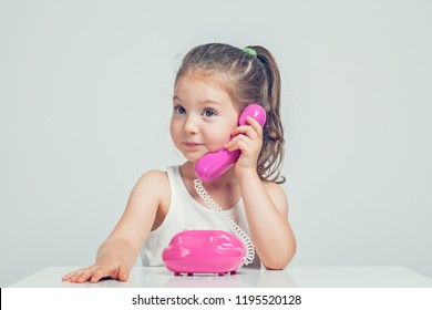 beautiful cute little girl talking on toy telephone with curious expression