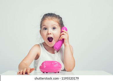 beautiful cute little girl talking on toy telephone with very excited expression