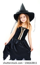 beautiful cute little girl in witch halloween costume smiling to the camera isolated over white
