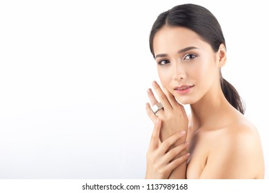 A beautiful cute smiling brunette with naked shoulders, nude make-up and shining healthy skin wears a large screw nut on the finger as a ring. Isolated on white. Copy space. Advertising design.