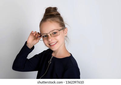 Beautiful cute smiling little girl with glasses looks to the camers