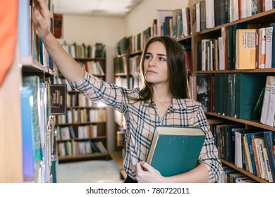 beautiful cute young girl in plaid shirt holds a large green book and gets another book of the shelf in the library