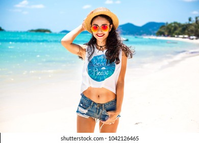 Beautiful cute young hipster girl at the seashore, dressed in a white jersey, denim shorts, thatched straw, mirror sunglasses, fashion accessories, vacation on a tropical island, travel, lifestyle
